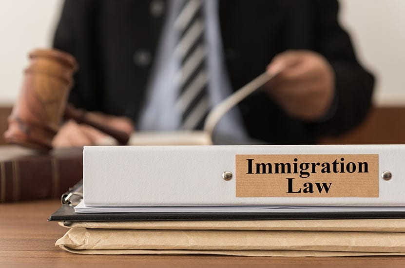 "A person sits behind a desk with the label ""Immigration Law"" on the desktop"