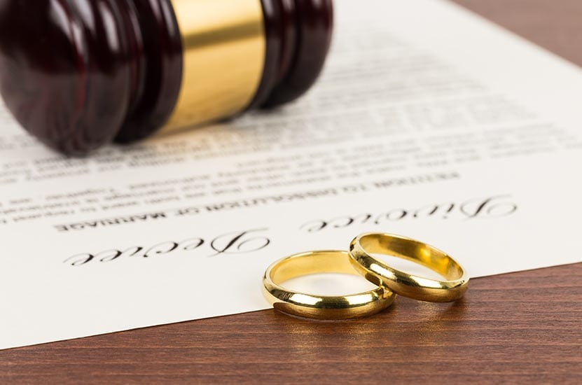 Two wedding rings sitting near divorce papers