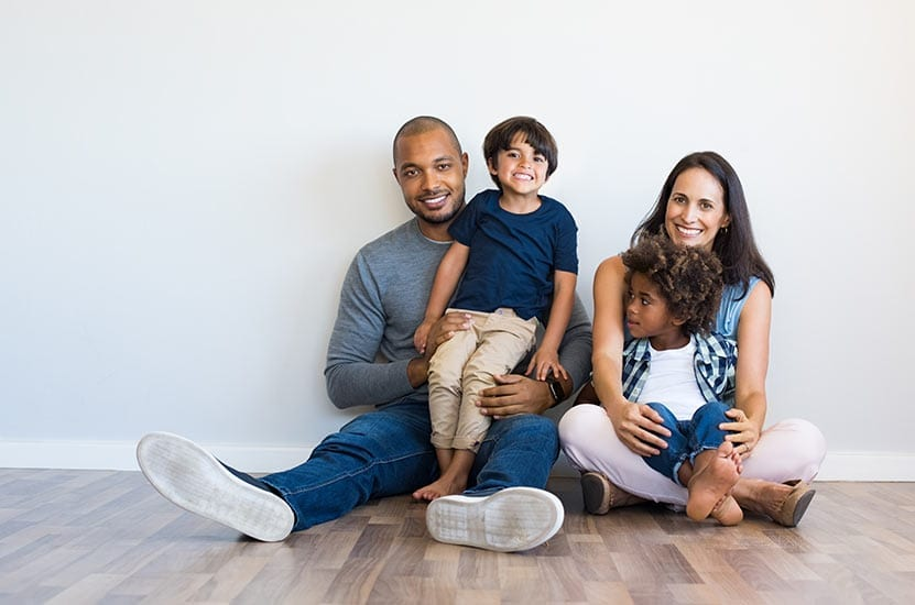 A family of four sitting in an empty room smiling
