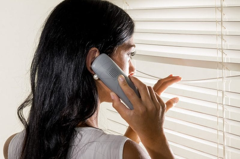 A woman peers outside her blinds while talking on the phone