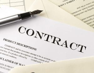 A contract sits in a pile of documents