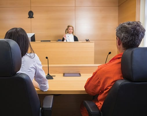 Lawyer and convict listen to a judge in a courtroom