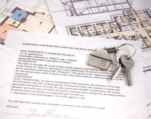 House keys, real estate agreement and house blueprints