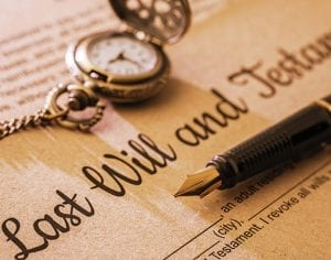 Pocket watch and ink pen sitting on a will and testament document